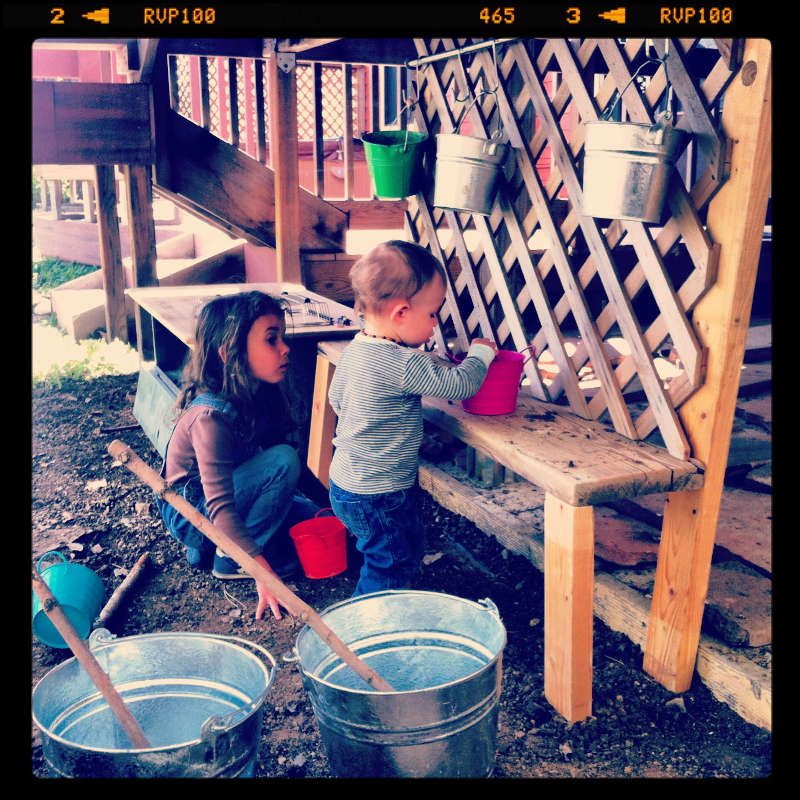 Nyla and Silas mixing potions in the rickety mud kitchen.