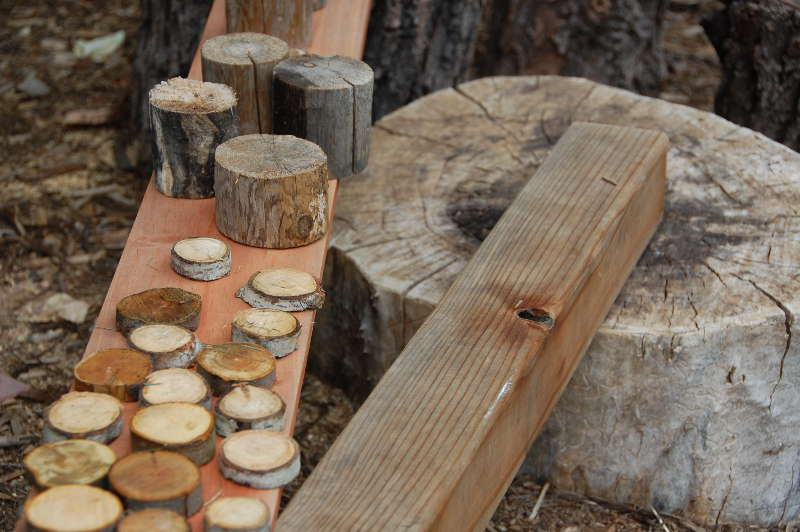 A collection of wooden loose parts, sourced from backyard tree cuttings, home improvement stores, and a local sawmill.