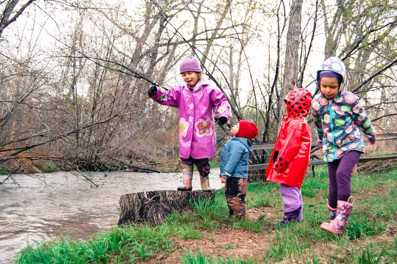The children—muddy, dripping wet, cold—stand near the rushing creek foraging for wild things in the rainy morning.