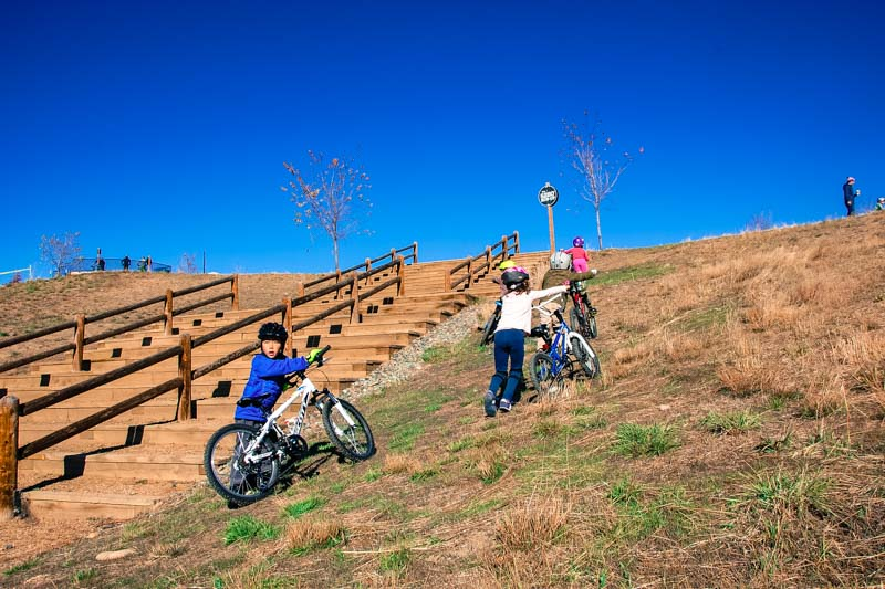 The pack of children avoids the stairs and pushes their heavy mountain bikes up the hill towards the Corkscrew.