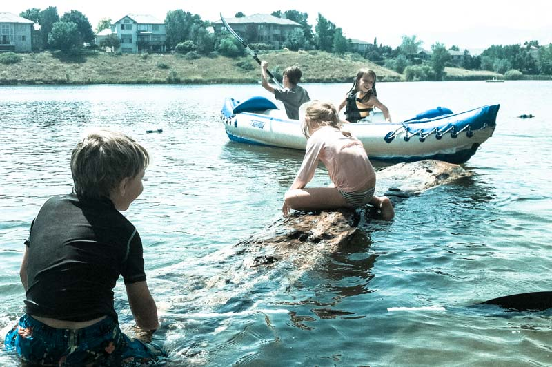 The children play on a giant log and inflatable kayak at an idyllic summer lake.