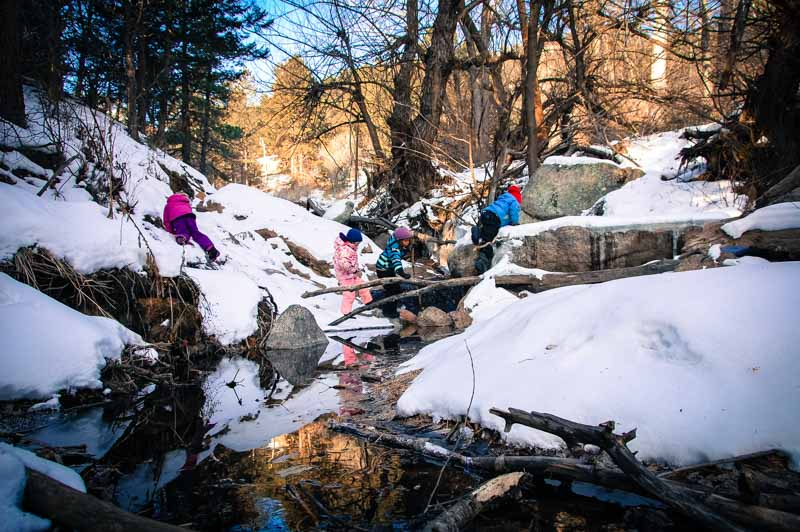 The children navigate a mountain stream, crossing en route to warmer lands.