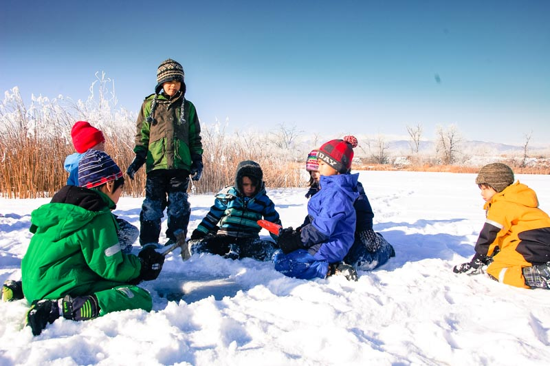 The children take turns with a hatchet and shovel, digging through the frozen surface of the ponds.