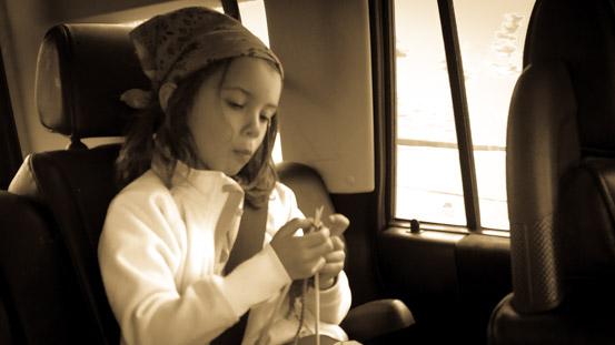 Nyla dreamily knitting on a drive