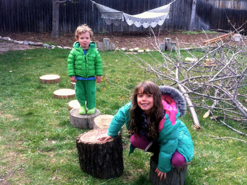 The children posing for a picture while playing with tree slices, tree stumps, apple tree branches, and in the background a 4x4 board propped on another tree stump. These loose parts are moveable by the children, and often become the chairs, tables, and walls for fine dining served up from the mud kitchen.