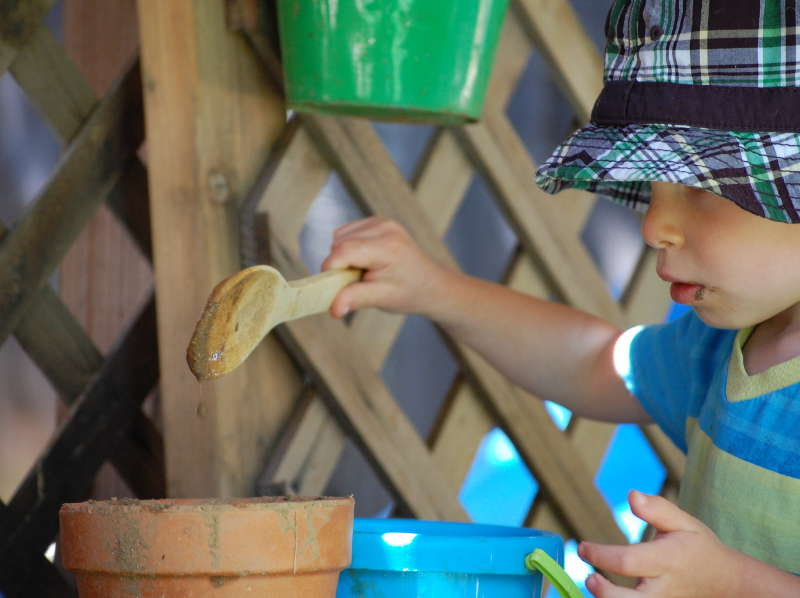 """Silas scoops """"hot cereal"""" carefully from the blue bucket to the terracotta bucket."""