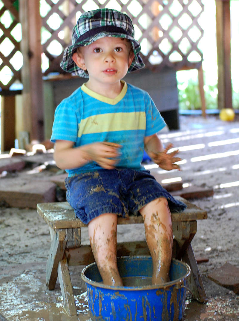 Silas enjoying a mud footbath at the children's pop-up spa behind the mud kitchen.