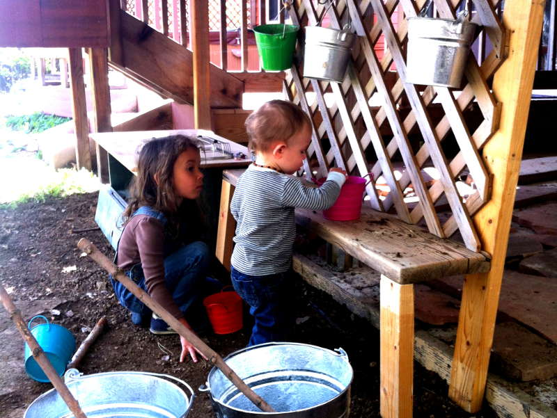Nyla and Silas playing on the counter in the mud kitchen, constructed from spare 2x4s, unused board, lattice, and IKEA kitchen hanger.