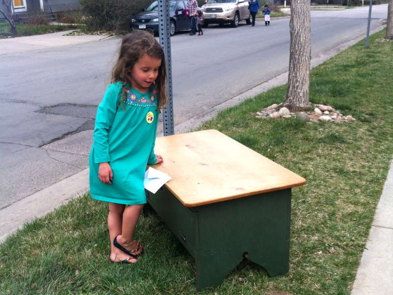 Nyla examining an antique desk offered for free on the curb as a candidate for the mud kitchen.