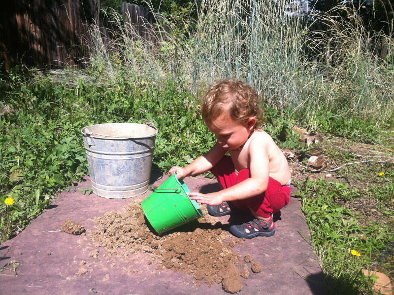Silas removing handfuls of mud, which has returned to dry fill dirt.
