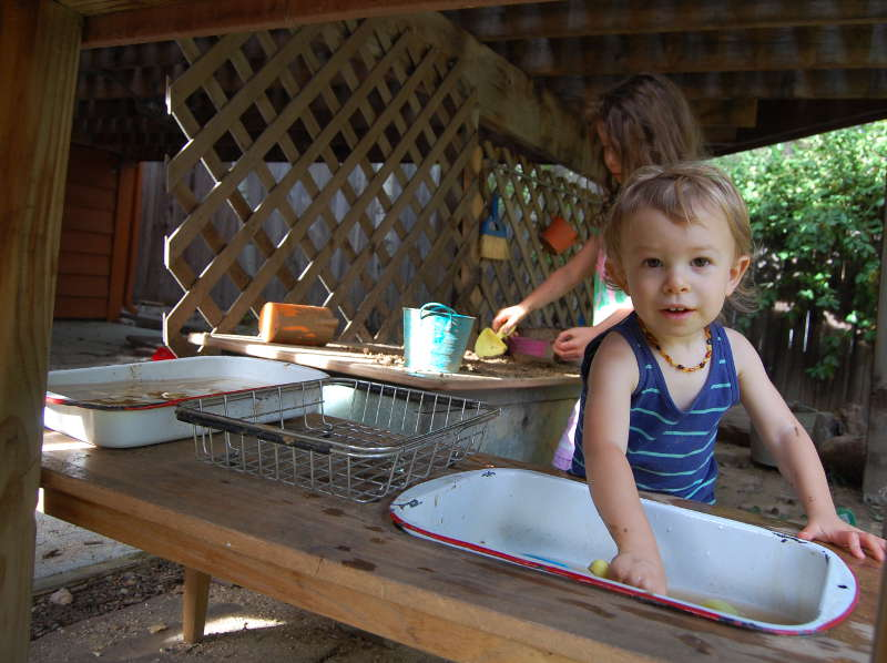 Silas doing dishes in the homemade sink.